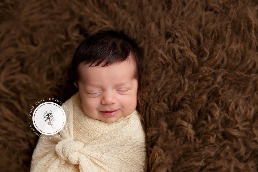 lachende_neugeborene_engelslaecheln_babyfotograf_anne_deml_muenchen_professionelle_babyfotos_hebamme_neugeborenenfotos_julie